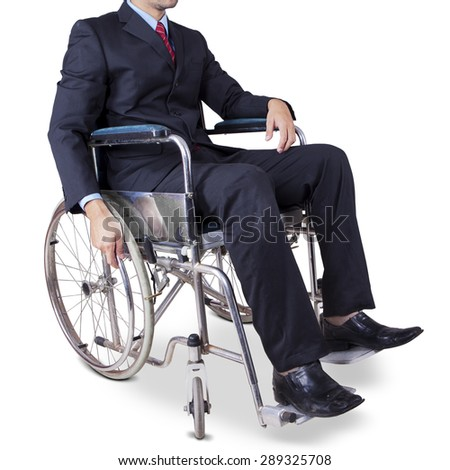 Businessperson with formal suit sitting on the wheelchair in the studio, isolated on white - stock photo