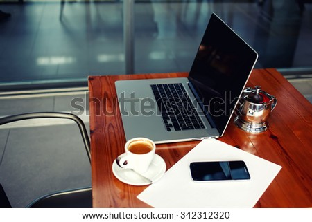 Businessperson work break, open laptop computer and smart phone gadget, portable net-book with cell telephone lying on a wooden table in coffee shop interior, freelance distance work, filtered image - stock photo