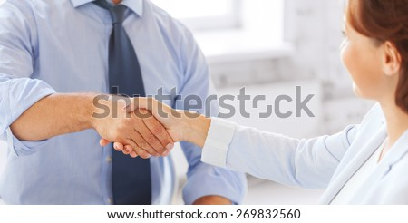 businesss and office concept - businessman and businesswoman shaking hands in office - stock photo