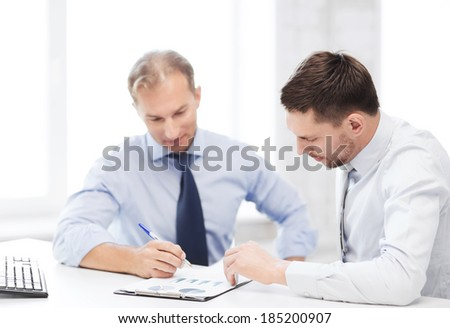 businesss concept - two businessmen discussing graphs on meeting