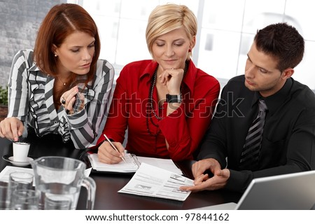 Businessteam at meeting, businesspeople reviewing documents, taking notes, working together. - stock photo
