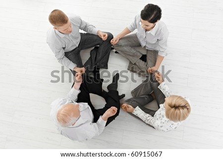 Businessteam doing yoga meditation together in smart clothes, sitting on floor, overhead view.?