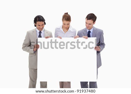 Businessteam looking at blank sign in their hands against a white background - stock photo