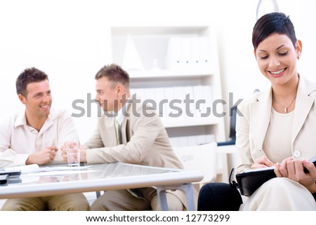 Businessteam of three working at office, businesswoman sitting in foreground, making notes, smiling. - stock photo