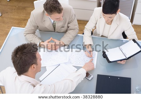 Businessteam of three working together, sitting around a desk, high angle view.