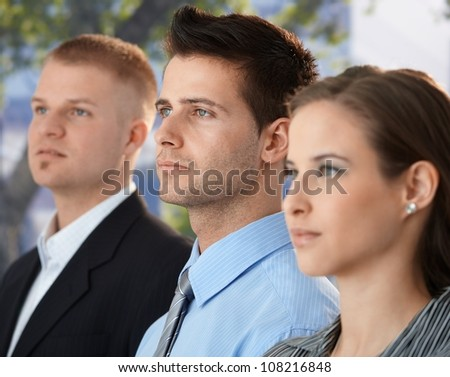 Businessteam outside, concentrating, standing together, focus on young businessman. - stock photo