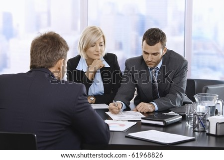 Businessteam reviewing documents together at meeting in office.? - stock photo