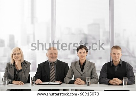 Businessteam sitting at meeting table, looking at camera, smiling.? - stock photo