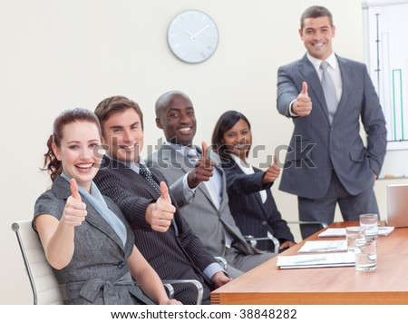 Businessteam with thumbs up after a presentation in office - stock photo