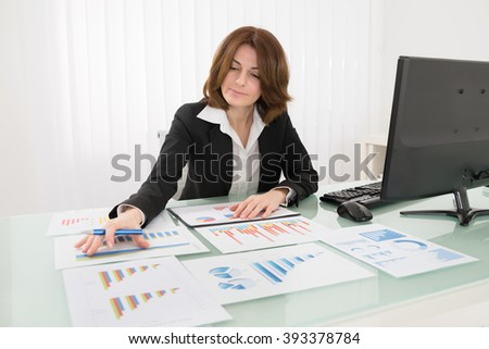 Businesswoman Analyzing Graph On Desk In Office