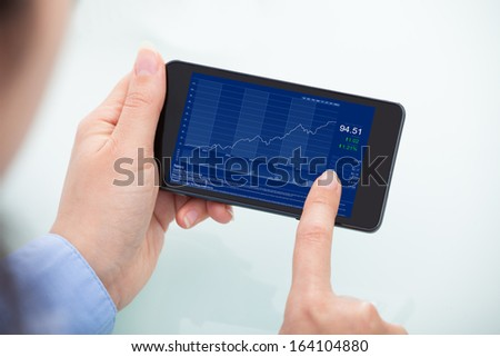 Businesswoman Analyzing Graph On Mobile Phone With Charts