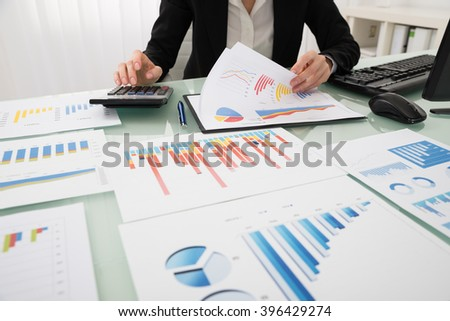 Businesswoman Analyzing Report On Chart With Calculator - stock photo