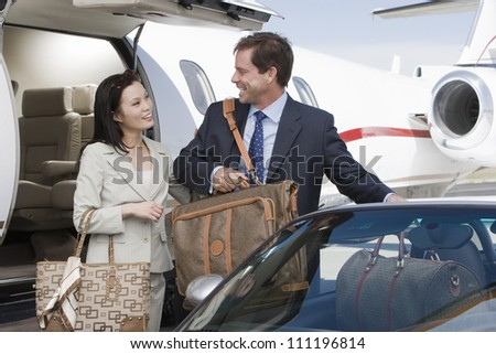 Businesswoman and businessman arrived to an airfield - stock photo