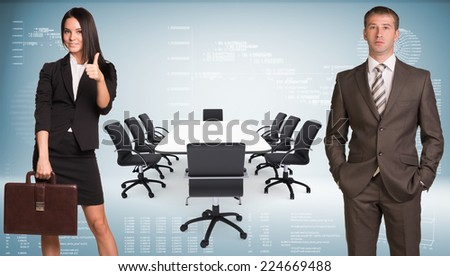 Businesswoman and businessman. Conference table, chairs and laptops as backdrop