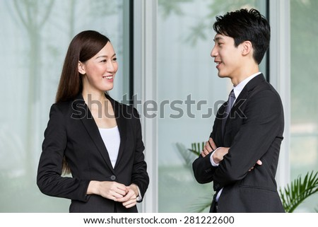 Businesswoman and businessman discuss together - stock photo
