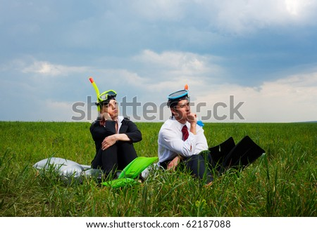 businesswoman and businessman in a melancholy mood and thinking about vacation - stock photo