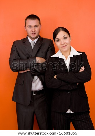 businesswoman and businessman in team standing on orange background