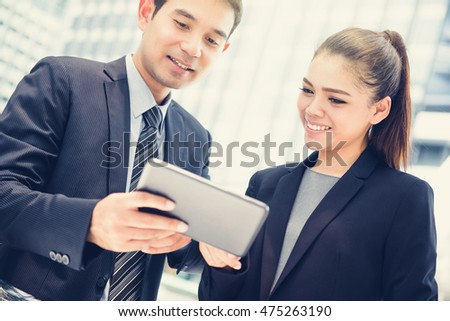 Businesswoman and businessman looking at tablet pc, vintage tone effect