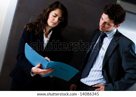 Businesswoman and businessman reviewing documents at office lobby in front of elevator. Dark background.