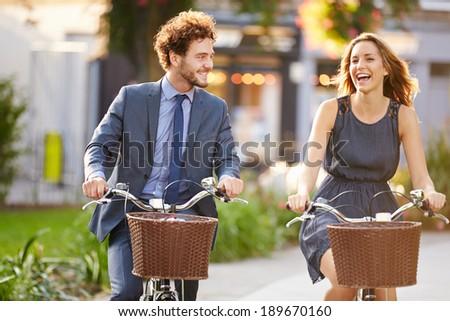 Businesswoman And Businessman Riding Bike Through City Park - stock photo