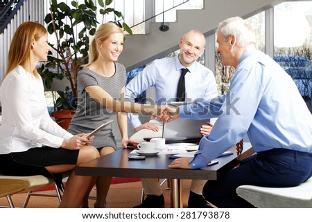Businesswoman and businessman shake hands across conference table while two business people smile beside them. - stock photo