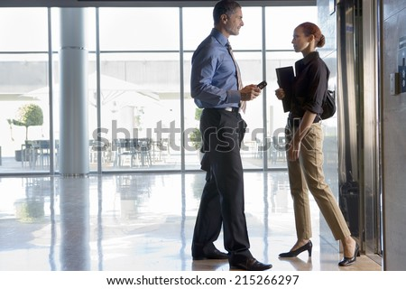 Businesswoman and businessman standing beside elevator in lobby, face to face, talking, profile