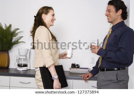 Businesswoman and businessman talking while having a break - stock photo
