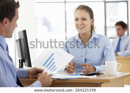 Businesswoman And Businessman Working At Desk Together - stock photo