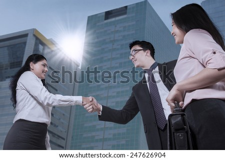 Businesswoman and client handshaking with a background of office building view - stock photo