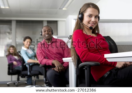 Businesswoman and co-workers working in cubicles - stock photo