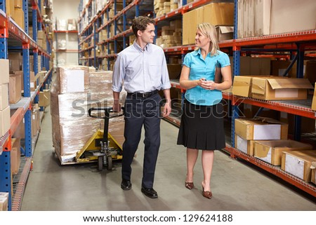 Businesswoman And Colleague In Distribution Warehouse - stock photo