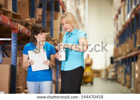 Businesswoman And Female Worker In Distribution Warehouse - stock photo