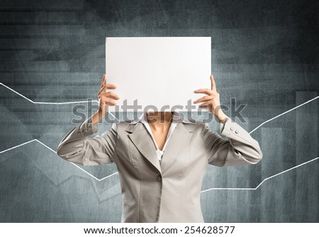 Businesswoman and graphs at background hiding her face behind paper