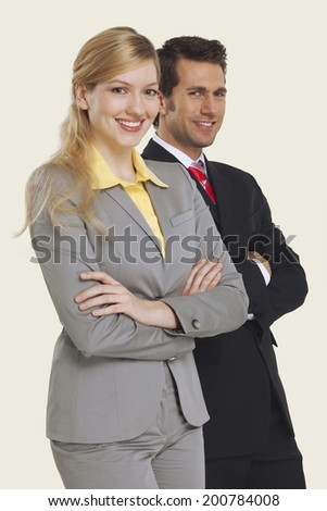 Businesswoman and man smiling, arms crossed. - stock photo