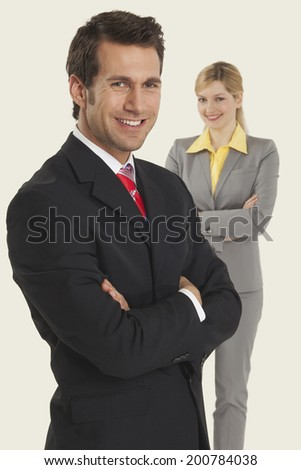 Businesswoman and man smiling, arms crossed.