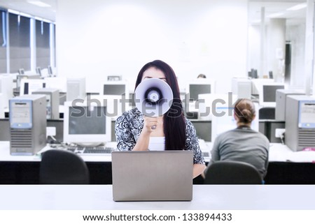 Businesswoman announce meeting at the office using megaphone