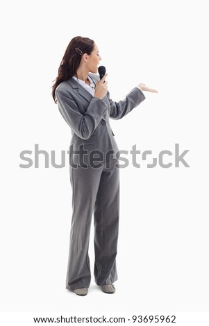 Businesswoman announcer speaking in a microphone and looking behind against white background - stock photo