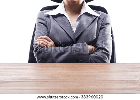 Businesswoman arms crossed sitting at the desk. - stock photo