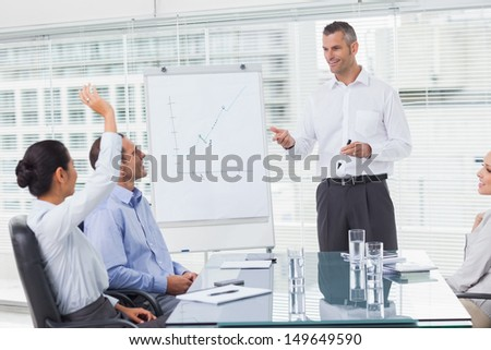 Businesswoman asking question during her colleagues presentation in bright office - stock photo