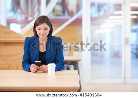 Businesswoman at a table smiling while reading her mobile phone - stock photo