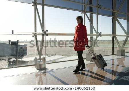 Businesswoman at airport traveling with trolley in red coat - stock photo