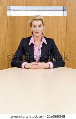 Businesswoman at conference table, hands clasped, portrait
