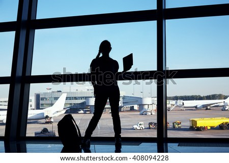 businesswoman at the airport. silhouette of a girl with mobile phone and backpack. business and travel - stock photo