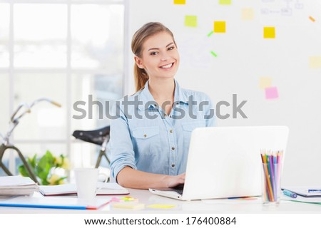 Businesswoman at work. Cheerful young businesswoman in casual wear using computer and smiling while sitting at her working place - stock photo