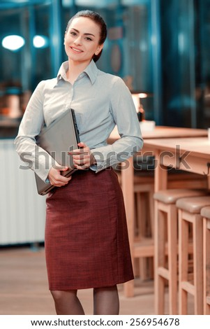Businesswoman at work. Portrait of beautiful young woman in formalwear smiling at camera while standing at the bar and holding laptop - stock photo