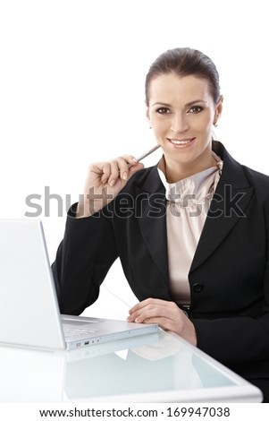 Businesswoman at work sitting at desk with laptop computer, smiling at camera with pen handheld. - stock photo