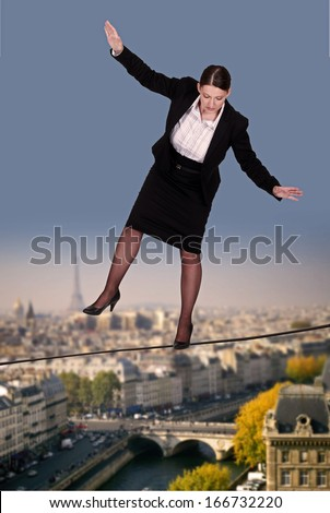 Businesswoman balancing on tight rope - stock photo