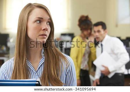 Businesswoman Being Gossiped About By Colleagues In Office - stock photo