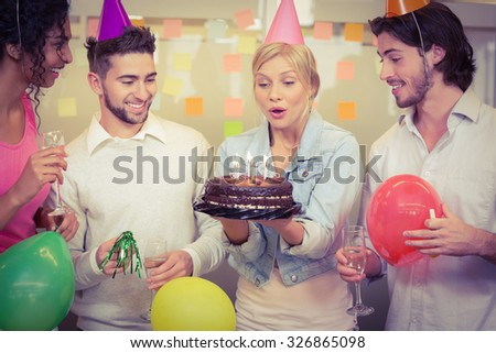 Businesswoman blowing birthday candles while colleagues looking at her in creative office - stock photo