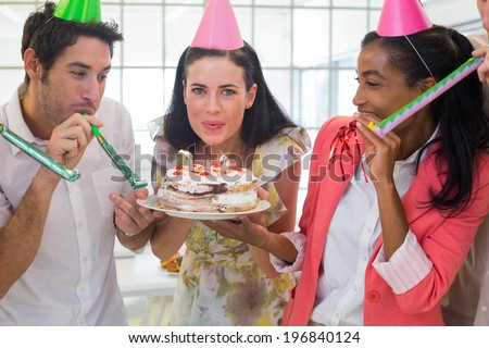 Businesswoman blowing out candles on cake in the office - stock photo